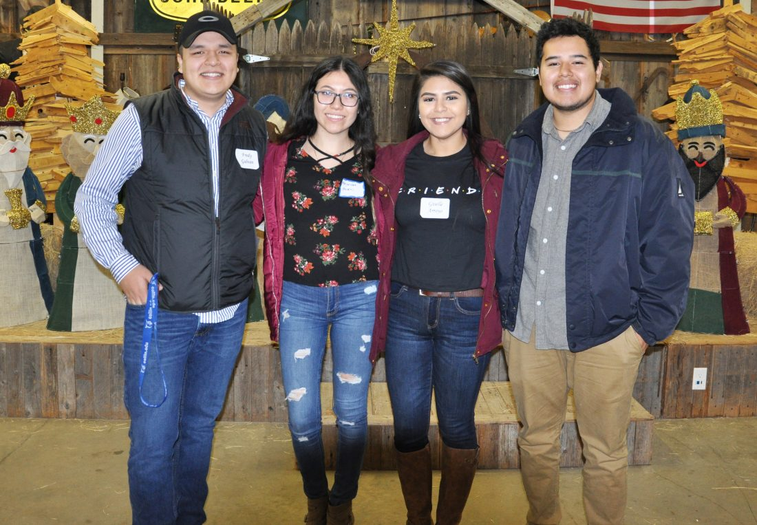 Four students posing for photo at holiday luncheon