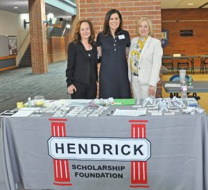 Three women standing behind table at the Hendrick Student Symposium