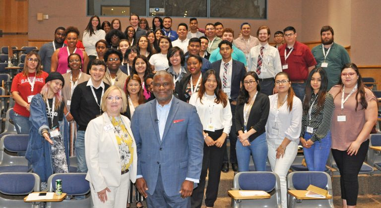 Students and leaders at the Hendrick Scholarship Foundation Symposium. Standing in auditorium.