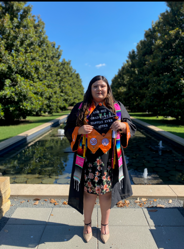 Ruby Mendoza standing in front of reflecting pool holding graduation cap