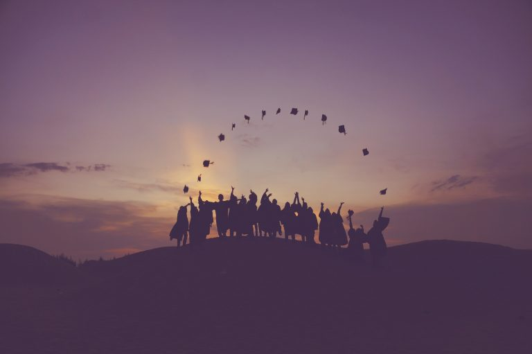 Group of graduates in hill top at sunset, throwing their caps into the air
