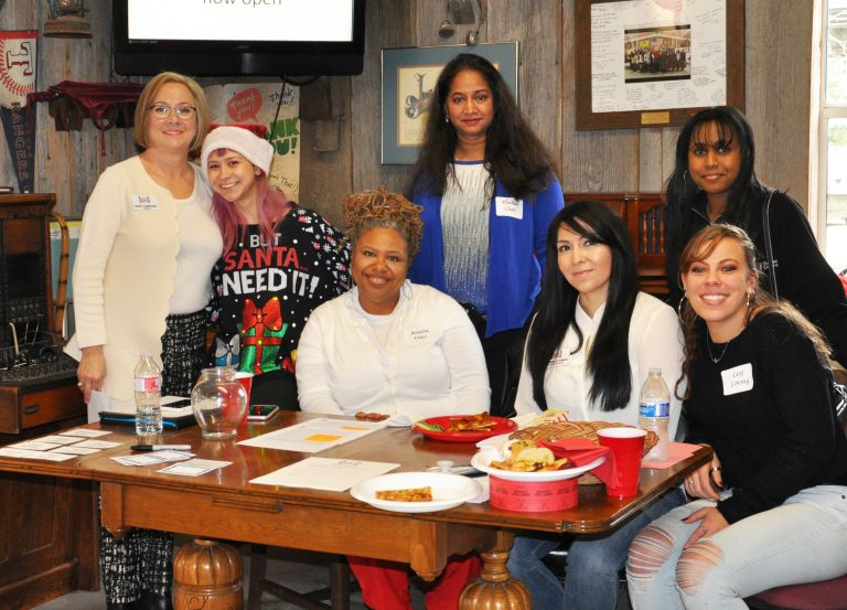 Group posing for a photo around a dining table at the foundation holiday luncheon