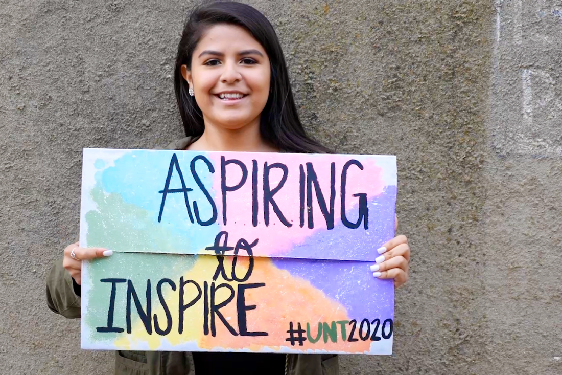 "Female student holding a sign which says ""aspiring to inspire #UNT2020"""