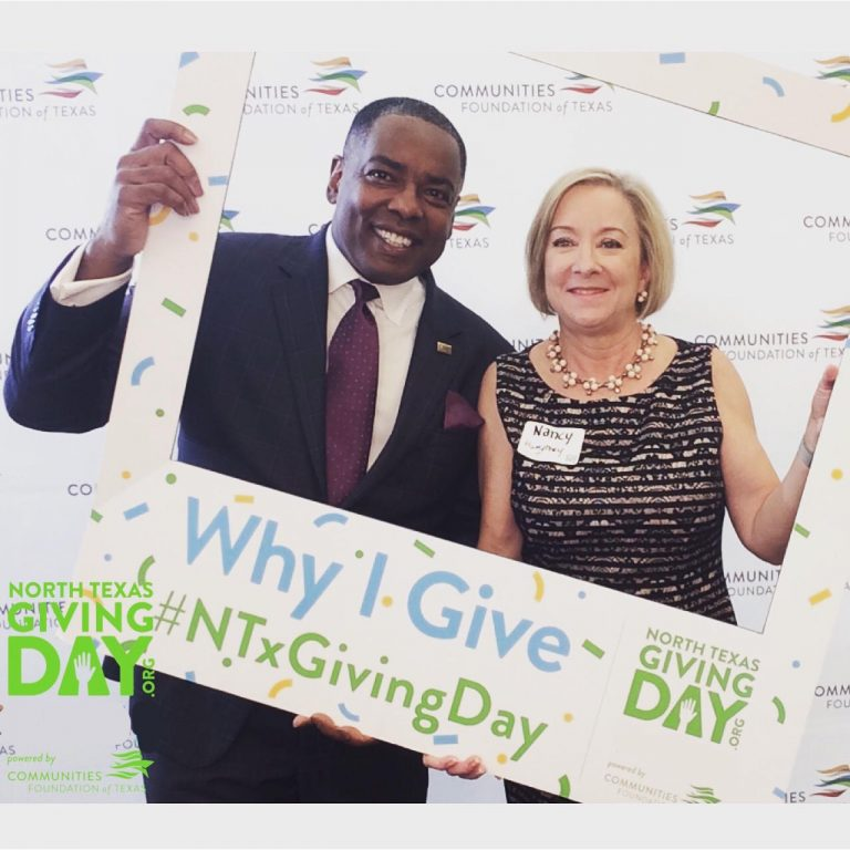 Man and woman peaking through large photo frame for North Texas Giving Day
